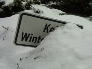 """Hinweisschild """"Kein Winterdienst"""", versunken im Schnee"""